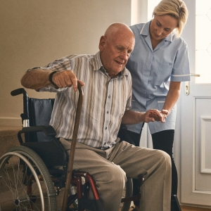 Female carer helping disabled senior man to get up from wheelchair at care home
